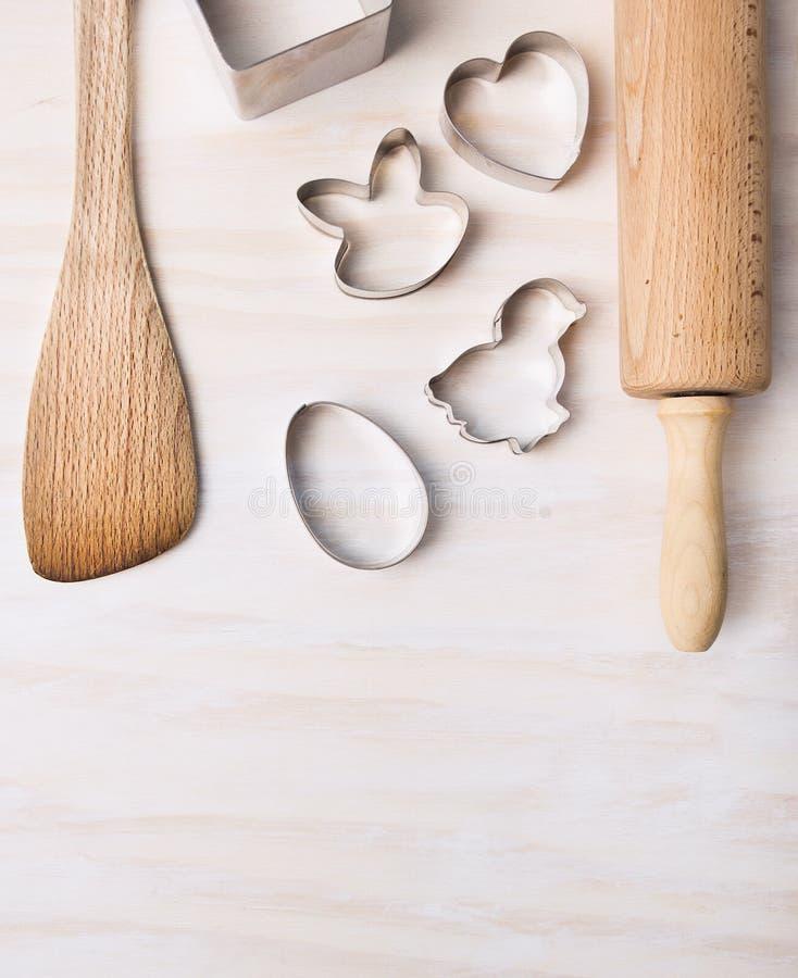 La cocina cuece los utensilios con los cortadores de la galleta de pascua en el fondo de madera blanco, visión superior fotografía de archivo