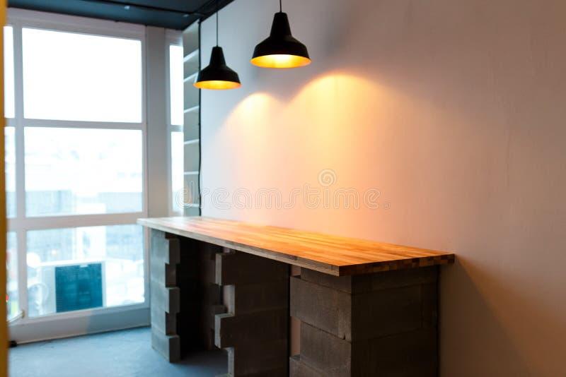 La cocina de la oficina con la tabla de madera y edison moderno se encienden diseño minimalistic del desván foto de archivo