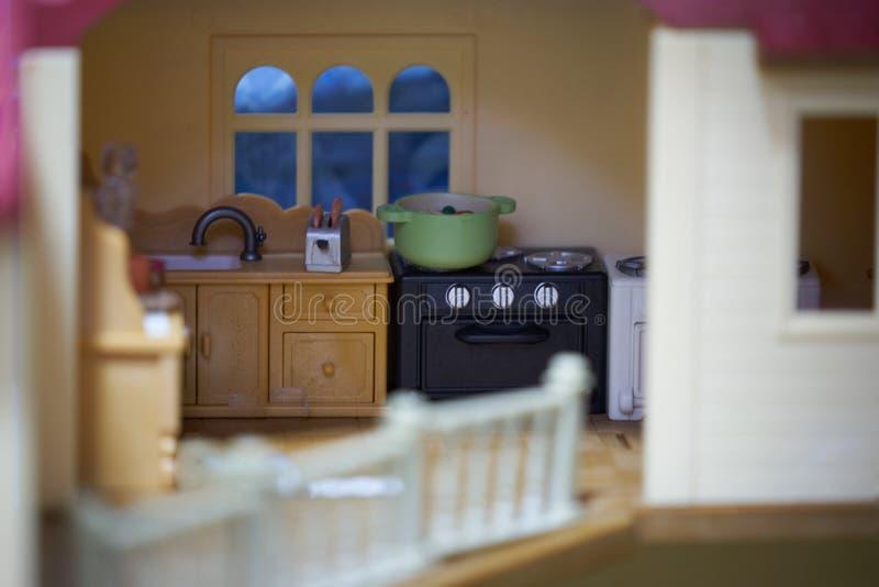 La cocina en casa del juguete incluye el pote, el fregadero, el panadero del pan y el horno fotografía de archivo