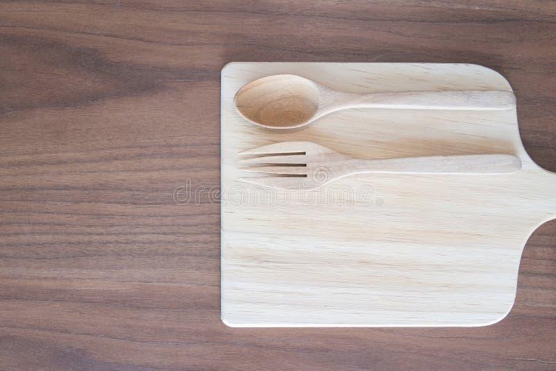La cocina era, el plato, la cuchara y la bifurcación de madera en la tabla de madera, top VI imagen de archivo