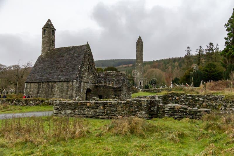La cocina y la torre redonda de Kevin del santo en el sitio monástico de Glendalough en Wicklow, Irlanda imágenes de archivo libres de regalías