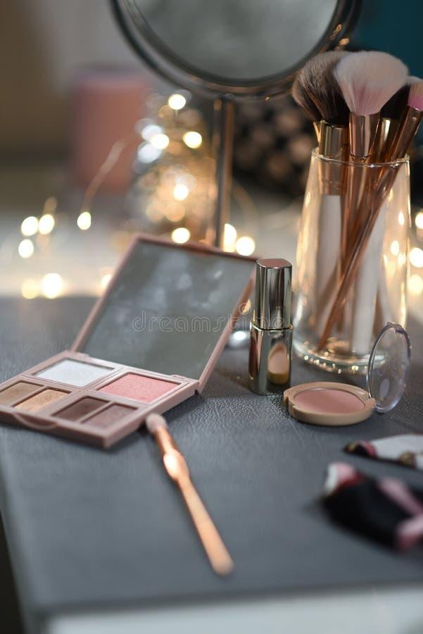 La coiffeuse avec le miroir, fards à paupières, rougissent, des approvisionnements de maquillage image libre de droits