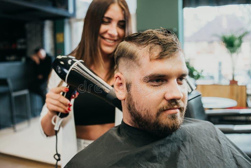 La coiffeuse de fille s?che des cheveux ? un homme dans un salon photographie stock libre de droits