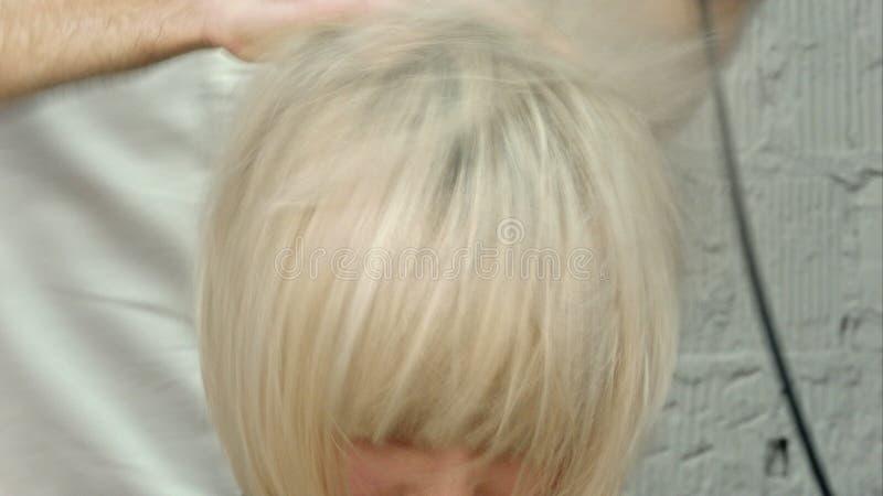 La coiffeuse de jeune femme font la fille de coiffure dans le salon de beauté photographie stock libre de droits