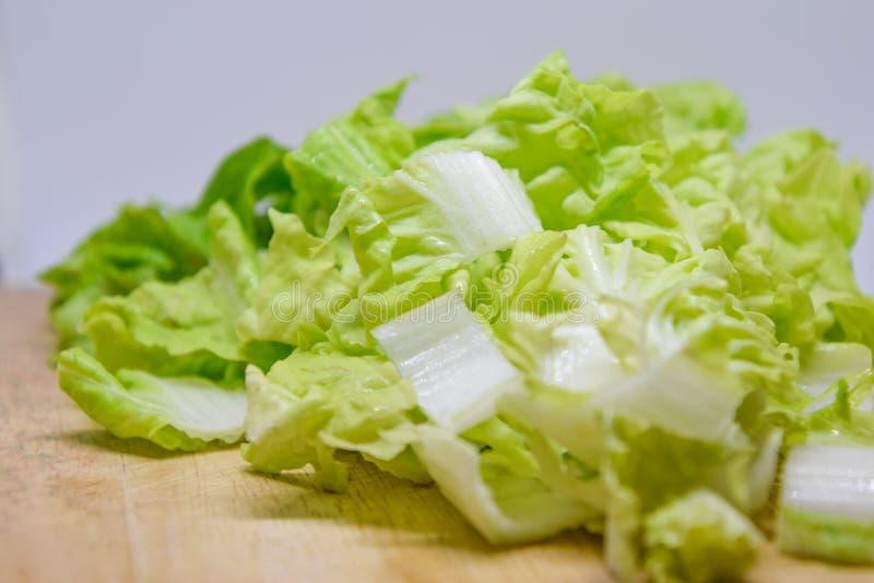 La col de China se corta en pedazos y colocado en una tabla de cortar de madera en el fondo blanco, cortar verduras se preparó pa imágenes de archivo libres de regalías