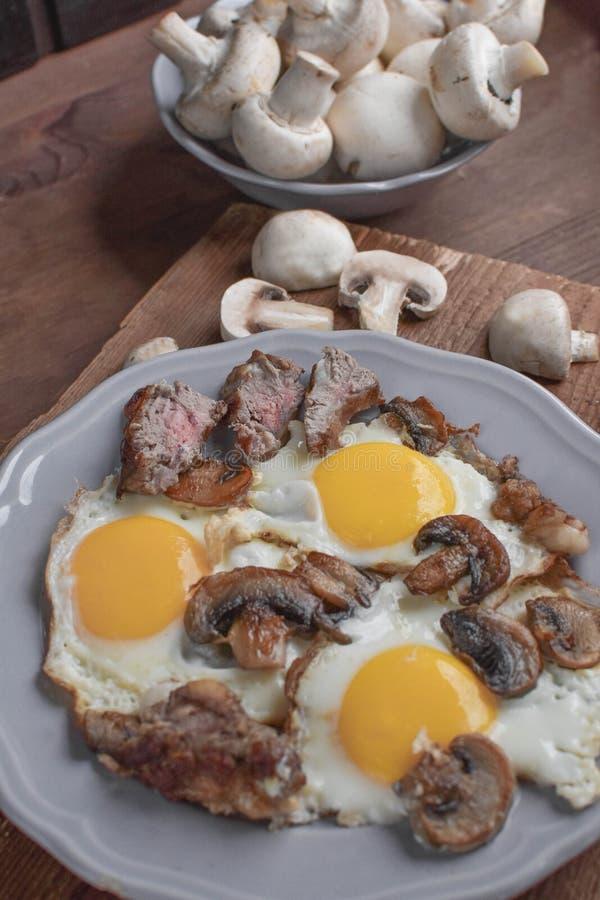 La colazione di un uomo, un uovo con funghi e carne per colazione - questo è un inizio meraviglioso della giornata fotografia stock libera da diritti