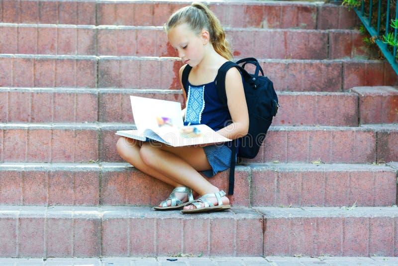 La colegiala 8 años que hacen la preparación en las escaleras lee el libro imagenes de archivo