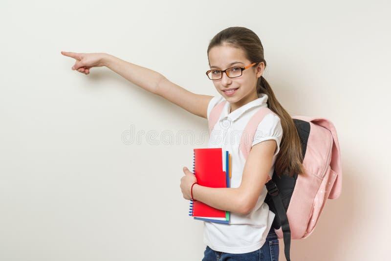 La colegiala de la muchacha 10 años con una mochila y los libros señala a foto de archivo