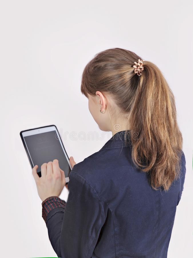 La colegiala del pelirrojo está sosteniendo la tableta digital con la pantalla en blanco vacía aislado sobre un fondo gris fotos de archivo libres de regalías