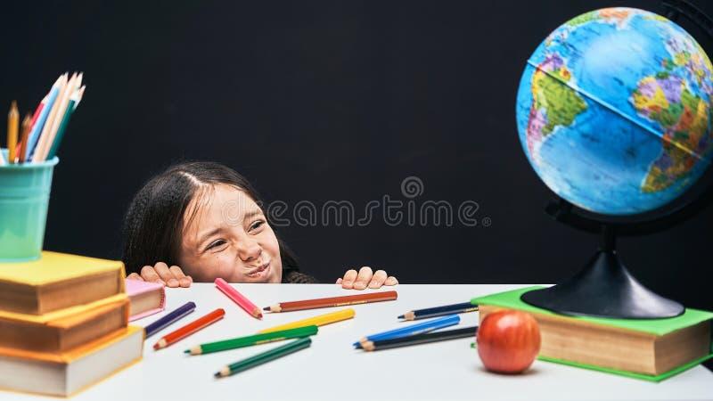 La colegiala divertida mira debajo de la tabla el concepto de la escuela en los lápices y los libros de la tabla con los libros d fotos de archivo libres de regalías