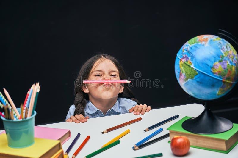 La colegiala divertida mira debajo de la tabla el concepto de la escuela en los lápices y los libros de la tabla con los libros d imagen de archivo libre de regalías