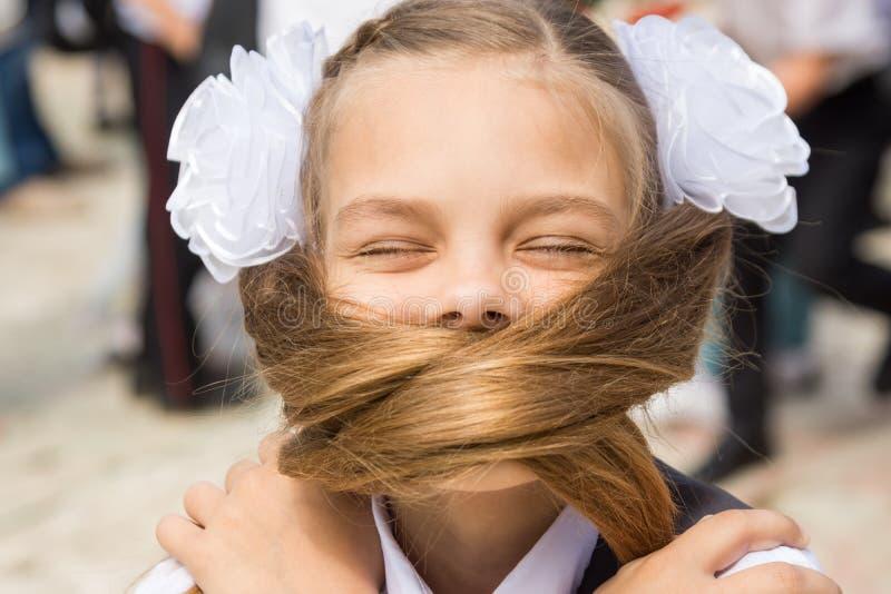 La colegiala el día de fiesta cubrió el 1 de septiembre su cara con su pelo largo fotos de archivo