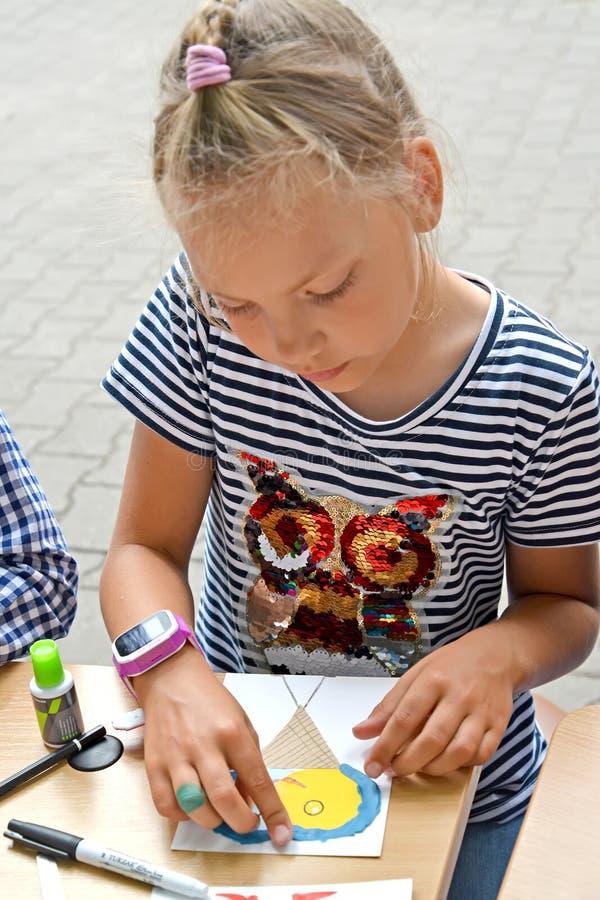 La colegiala hace applique del papel del plasticine Clase del amo del ` s de los niños en el aire abierto imágenes de archivo libres de regalías