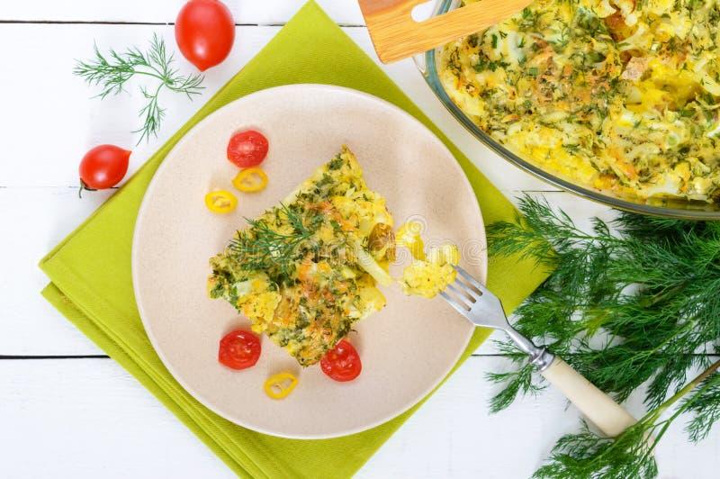 La coliflor coció con queso, verdes y el huevo Un pedazo grande en una placa imagen de archivo