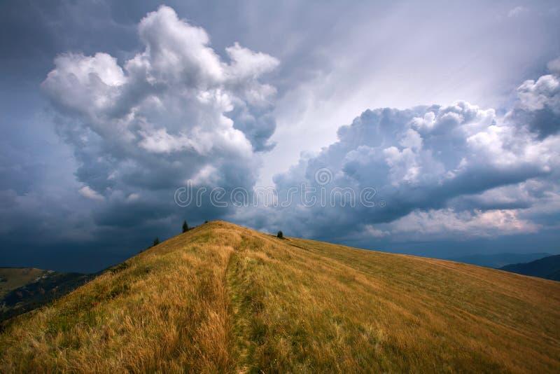 La colina en montañas en el fondo de las nubes de tormenta dramáticas del cielo imagen de archivo