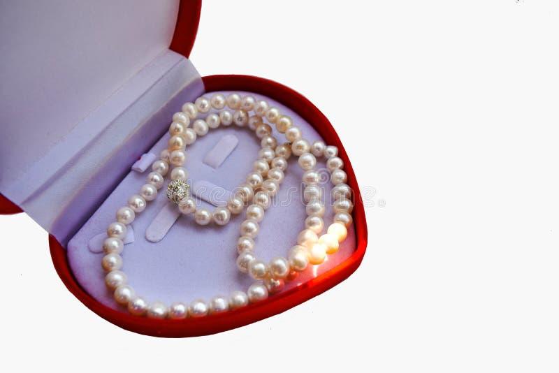 La collana bianca della perla su una scatola rossa è una forma del cuore fotografia stock