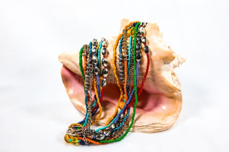 La collana multistrand multicolore di boho con il piccolo segno di pace ha coperto sopra una conchiglia di strombo su fondo bianc immagini stock libere da diritti
