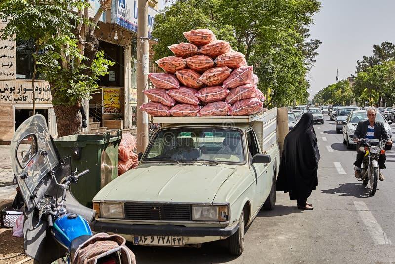 La collecte a chargé avec des sacs des carottes sur la rue de ville, Iran image libre de droits