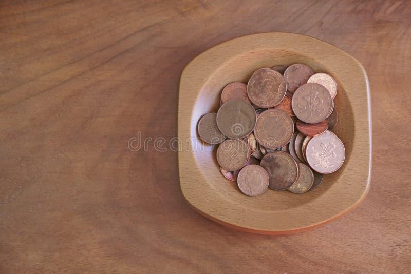 La collection invente l'épargne de cuivre de penny dans la cuvette en bois images stock