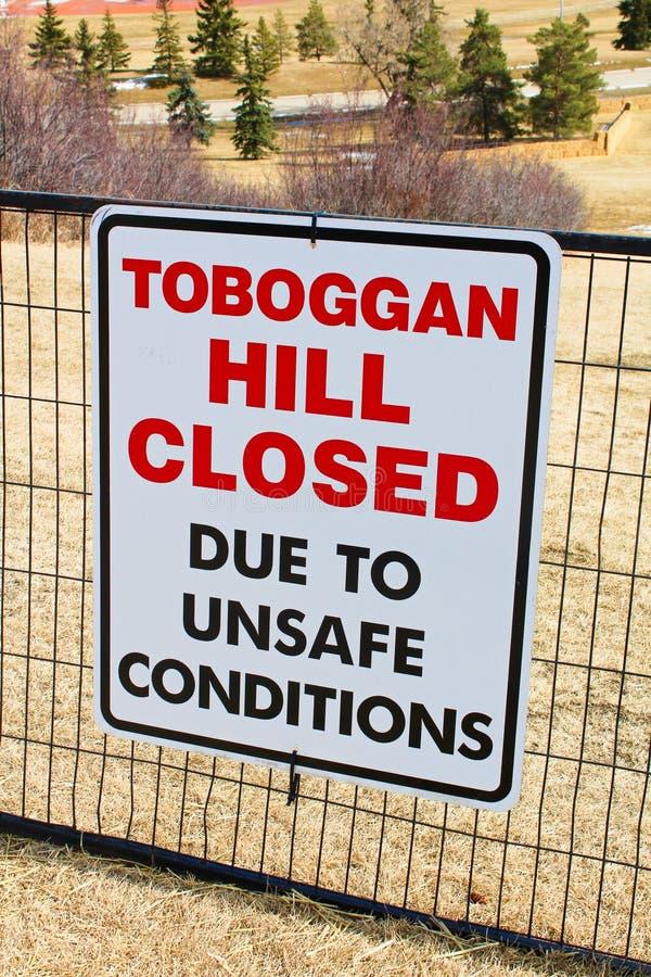 La colline de toboggan a fermé le signe signalé en parc public une fois que toute la neige a fondu photographie stock