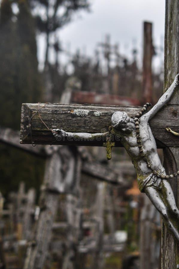 La colline des croix en Lithuanie avec un tir de detail's d'une croix simple avec un chiffre de Jésus a accentué photo stock