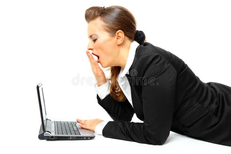 La colocación en suelo cansó a la mujer de negocios con la computadora portátil imagenes de archivo