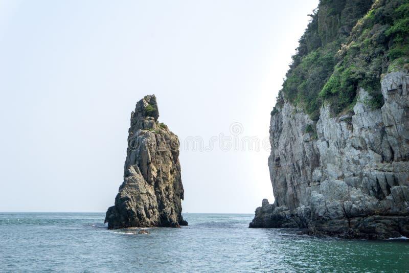La colonna di pietra è emerso dal mare è la parte delle isole della roccia di Geoje Haegeumgang fotografie stock libere da diritti