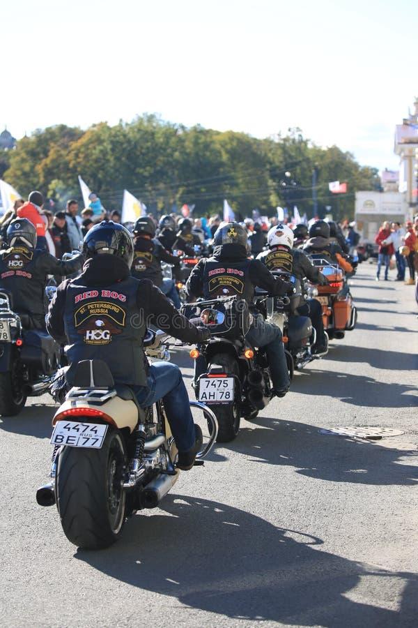 La colonne des PROPRIÉTAIRES de HARLEY russes GROUPENT des cyclistes sur la place de palais photos libres de droits