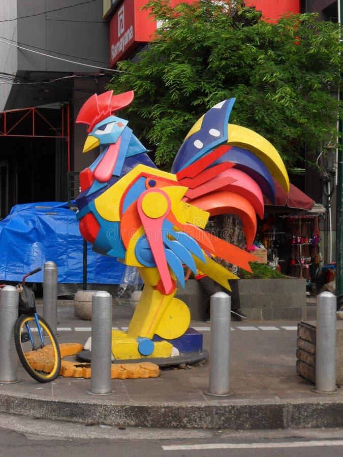 La colorida estatua de pollo en madera foto de archivo