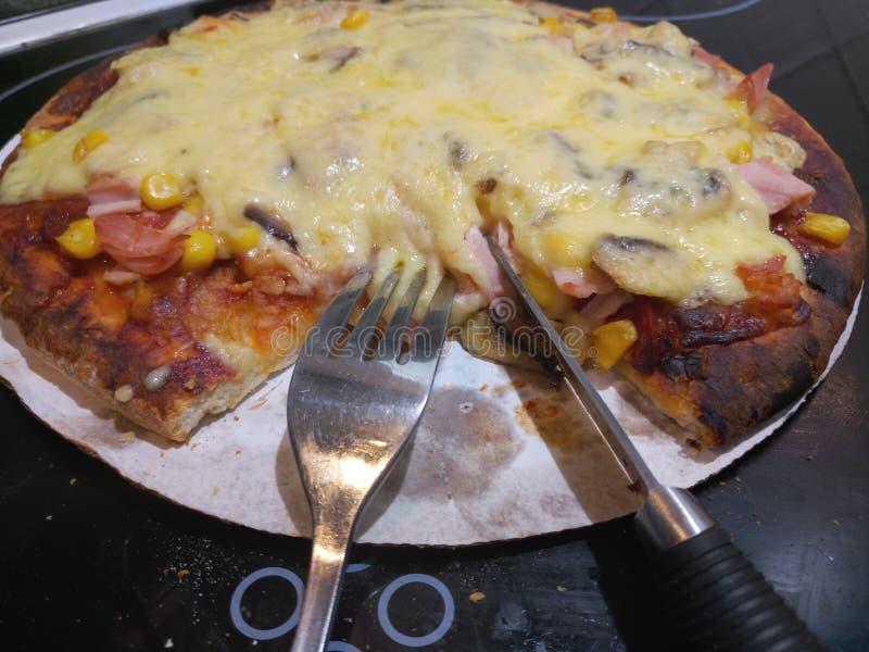 La coltelleria d'argento su un giro kitsch ha cucinato la pizza fotografia stock libera da diritti