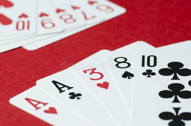 La combinaison des cartes dans le tisonnier sur un fond rouge photographie stock libre de droits