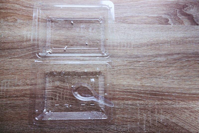 La comida desecha el arroz en caja y cuchara plásticas transparentes de la comida en la tabla de madera imagenes de archivo