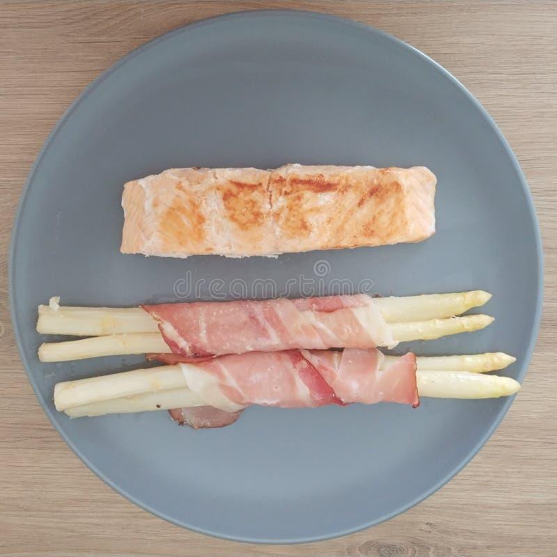 La comida quetogénica, los pescados de color salmón con tocino envolvió el espárrago blanco Comida del Keto para la pérdida de pe foto de archivo
