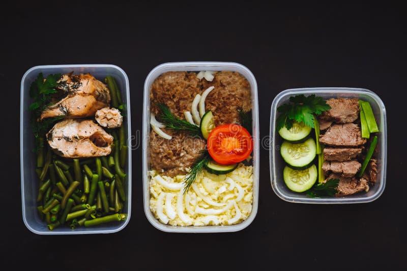 La comida sana en los envases en fondo negro: bocado, cena, almuerzo Pescados cocidos, habas, chuletas de la carne de vaca, purés imagen de archivo
