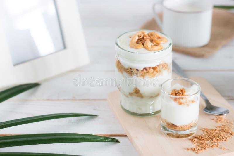 La comida sana hecha del granola en vidrio, el yogur y los copos de maíz adornan la comida con el anacardo por otra parte tiene p fotos de archivo