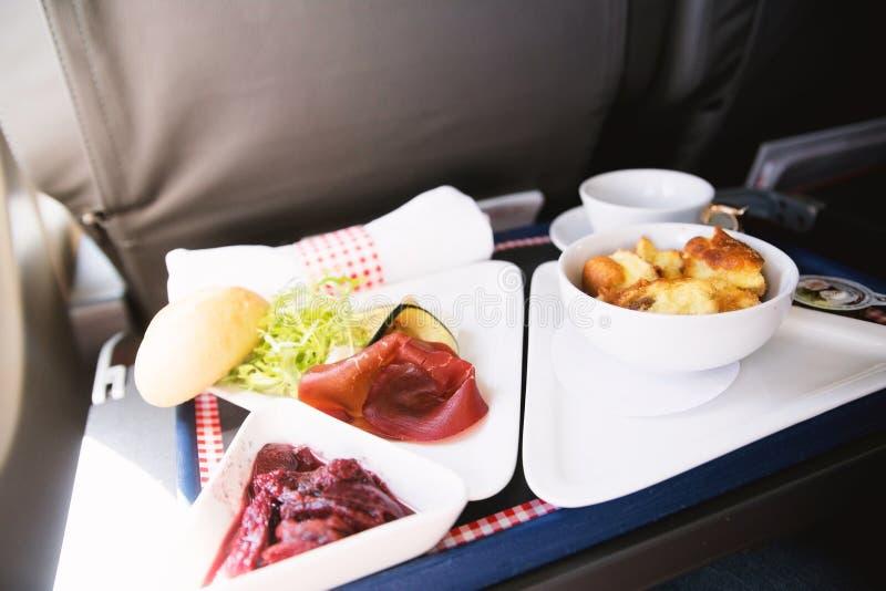 La comida sirvió a bordo del aeroplano de la clase de negocios en la tabla fotos de archivo