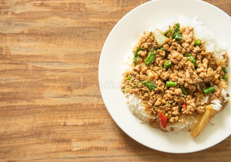 La comida tailandesa, cerdo sofrito con albahaca se va en backgroun de madera fotografía de archivo libre de regalías