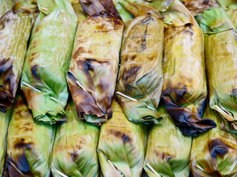 La comida tailandesa de la calle, asó a la parrilla el arroz pegajoso con el taro y el plátano imágenes de archivo libres de regalías