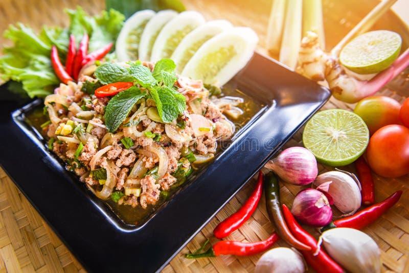 La comida tailandesa de la ensalada picadita picante del cerdo sirvió en la tabla con las hierbas y los ingredientes de las espec imágenes de archivo libres de regalías