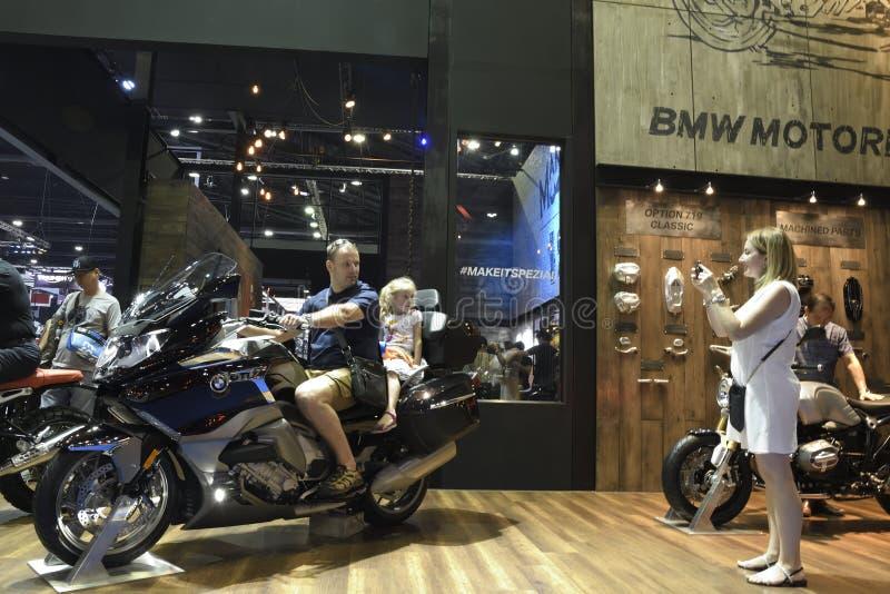 La commande d'essai d'Amily et prennent la photo avec la moto de BMW dans l'exposition de cabine de BMW au trente-neuvième SALON  image libre de droits