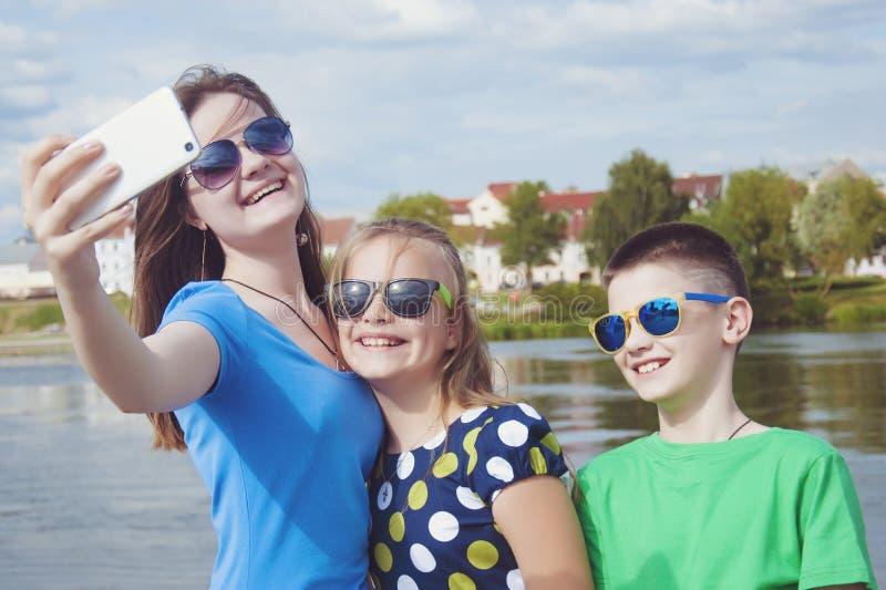 La compañía alegre del ` s de los niños hace el selfie en un smartphone en una calle de la ciudad al aire libre fotografía de archivo libre de regalías