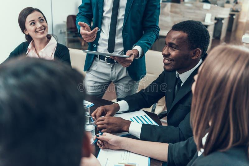 La compañía multinacional de hombres de negocios celebra la reunión en sala de conferencias imagenes de archivo