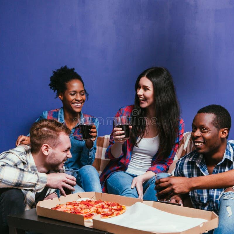 La compañía sonriente se divierte en casa, partido caliente de la pizza fotos de archivo