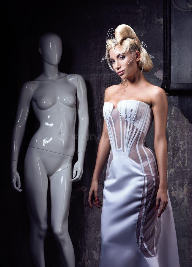 La comparación de la mujer y del maniquí Mujer joven hermosa en el vestido de anat-Garde fotos de archivo libres de regalías