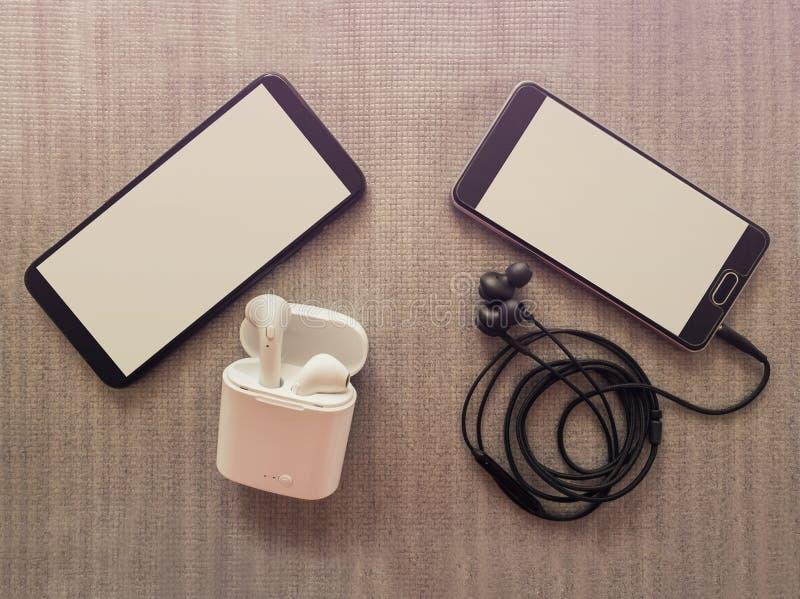 La comparación entre dos teléfonos, una tiene 3 el enchufe de 5m m ató con alambre los auriculares contra los auriculares inalámb foto de archivo