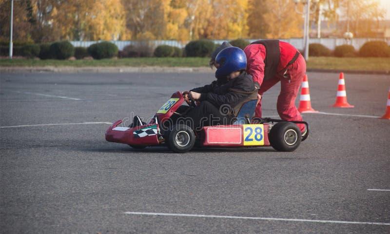 La competencia de Karting, el participante empuja al hombre joven en karting para karting, conductor foto de archivo libre de regalías