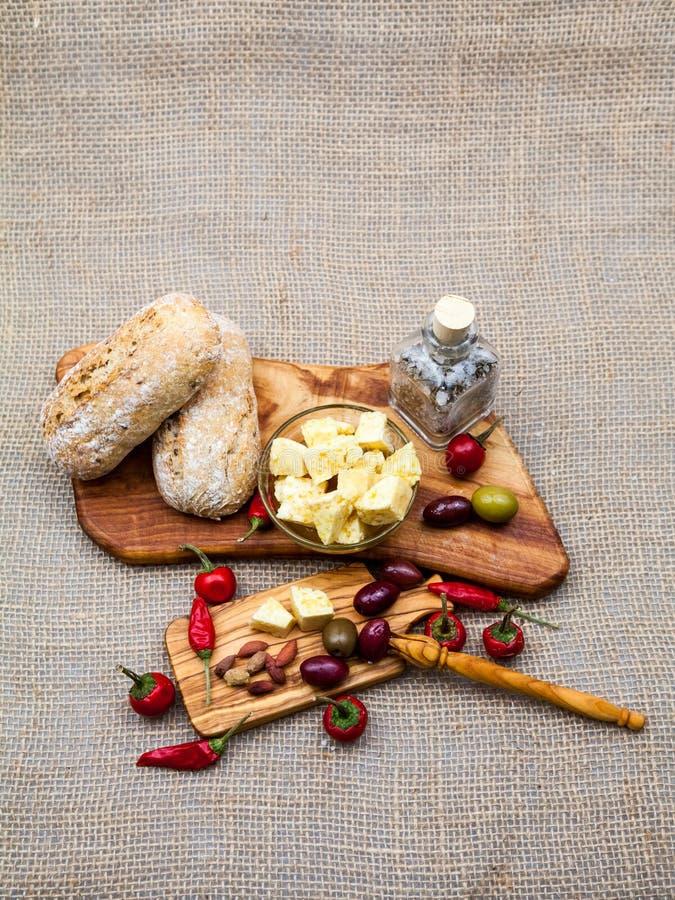 La composición con la madera verde oliva, aceitunas, pan, queso junta las piezas en el aceite de oliva, especias imagen de archivo