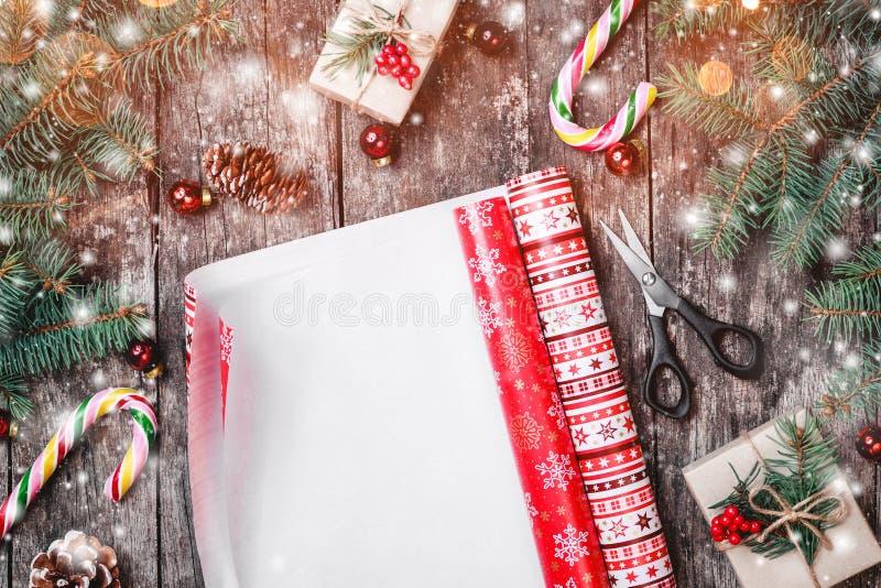 La composición con Navidad que envuelve, abeto de la Navidad ramifica, los regalos, conos del pino, decoraciones rojas en fondo d imagen de archivo libre de regalías