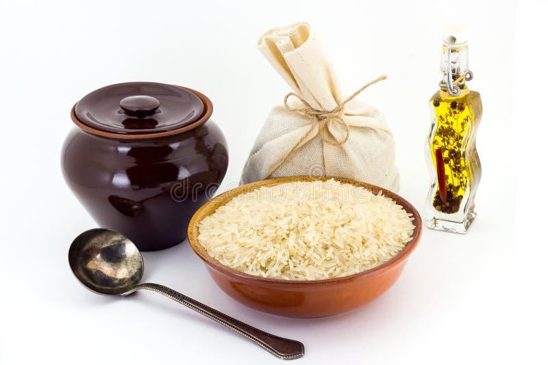 La composición de las avenas mondadas del arroz Steamed en una arcilla pial al lado de un pote de arcilla y de una cuchara de cob fotos de archivo