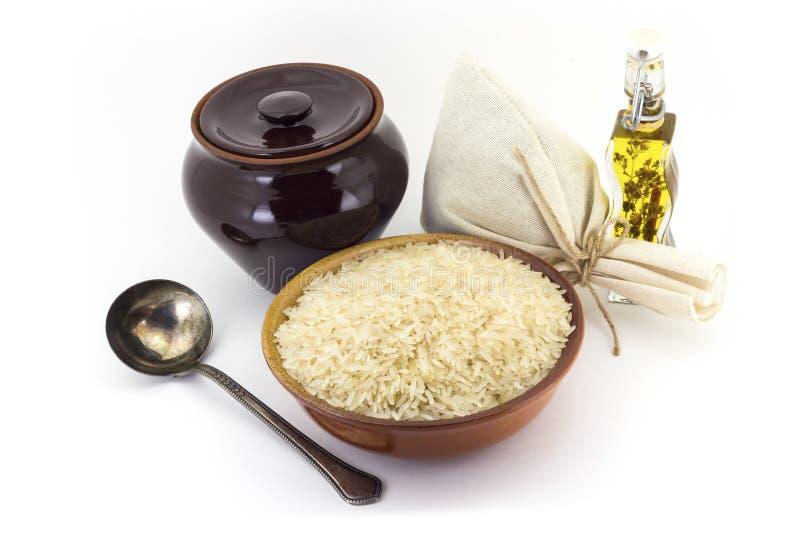 La composición de las avenas mondadas del arroz Steamed en una arcilla pial al lado de un pote de arcilla y de una cuchara de cob foto de archivo